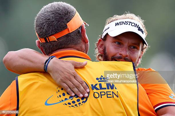 Joost Luiten of the Netherlands celebrates victory with his caddie Mike Waite on the 18th green during the final round on day four of the KLM Open at...