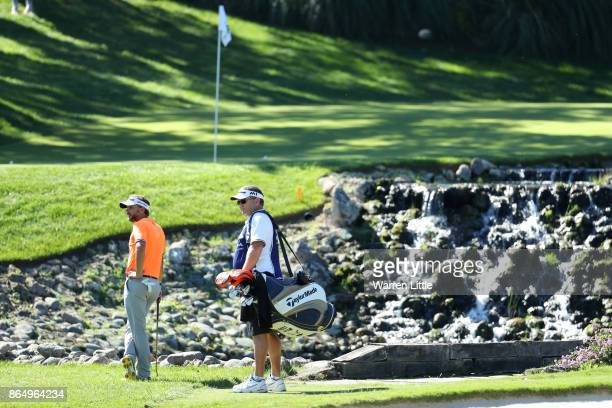 Joost Luiten of the Netherlands looks on with caddie Mike Waite on the 4th hole during the final round of of the Andalucia Valderrama Masters at Real...