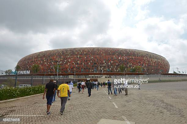 Joournalists arrive for a briefing on December 8 2013 at the FNB Stadium in Johannesburg where the memorial ceremony for South African former...