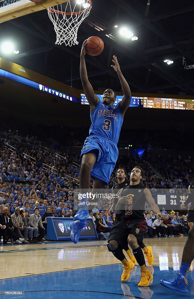 Jordan Adams #3 of the UCLA Bruins drives to the basket for a layup past Chass Bryan #13 of the USC Trojans in the second half at Pauley Pavilion on January 30, 2013 in Los Angeles, California. USC defeated UCLA 75-71 in overtime.