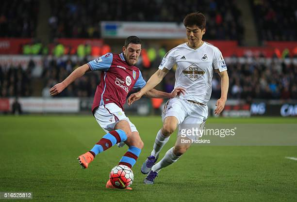 Jordan Ayew of Aston Villa and Ki SungYeung of Swansea City compete for the ball during the Barclays Premier League match between Swansea City and...