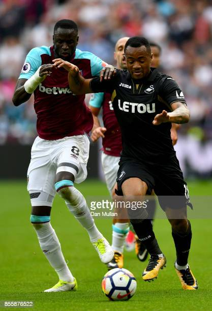 Jordan Ayew of Swansea City and Cheikhou Kouyate of West Ham United compete for the ball during the Premier League match between West Ham United and...