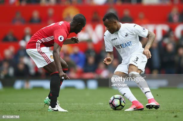 Jordan Ayew of Swansea City attempts to take the ball past Eric Bailly of Manchester United during the Premier League match between Manchester United...