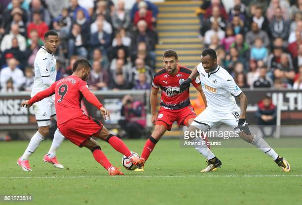 Jordan Ayew of Swansea City challenges Elias Kachunga of Huddersfield Town during the Premier League match between Swansea City and Huddersfield Town...