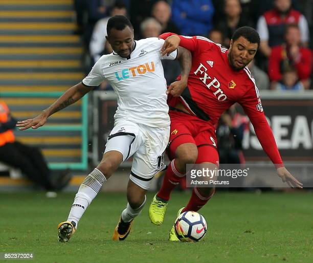 Jordan Ayew of Swansea City challenges Troy Deeney of Watford during the Premier League match between Swansea City and Watford at The Liberty Stadium...