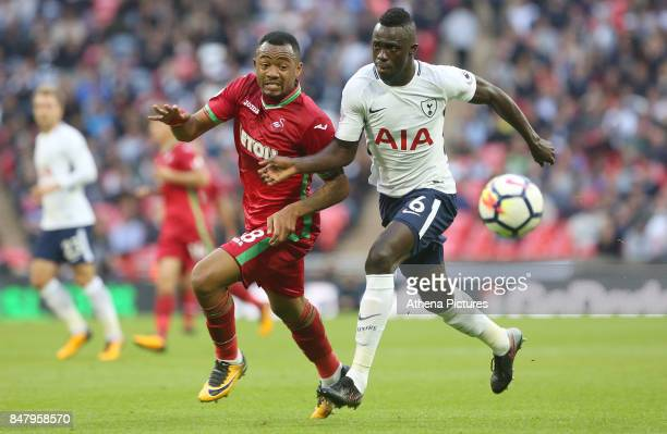 Jordan Ayew of Swansea City is challenged by Davinson Sanchez of Tottenham Hotspur during the Premier League match between Tottenham Hotspur and...