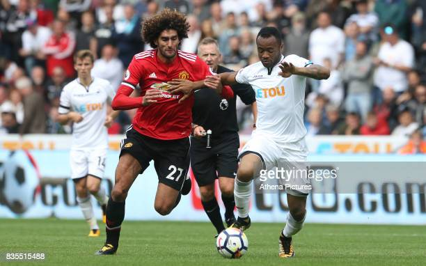 Jordan Ayew of Swansea City is challenged by Marouane Fellaini of Manchester United during the Premier League match between Swansea City and...