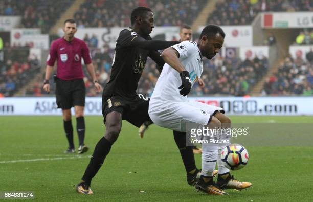 Jordan Ayew of Swansea City is marked by Wilfred Ndidi of Leicester City during the Premier League match between Swansea City and Leicester City at...