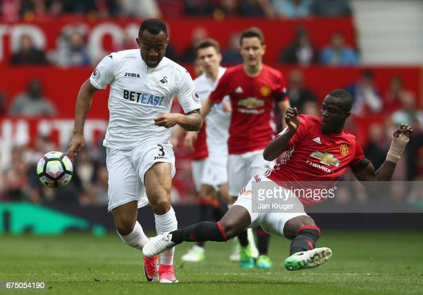 Jordan Ayew of Swansea City is tackled by Eric Bailly of Manchester United during the Premier League match between Manchester United and Swansea City...