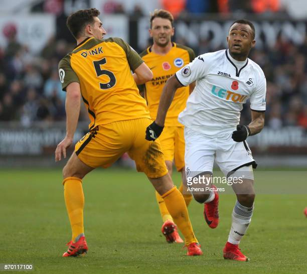 Jordan Ayew of Swansea City looks up to the ball while marked by Lewis Dunk of Brighton during the Premier League match between Swansea City and...