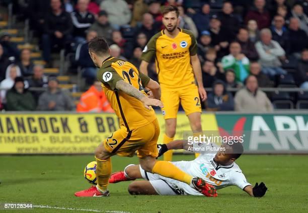 Jordan Ayew of Swansea City slide tackles Shane Duffy of Brighton during the Premier League match between Swansea City and Brighton and Hove Albion...