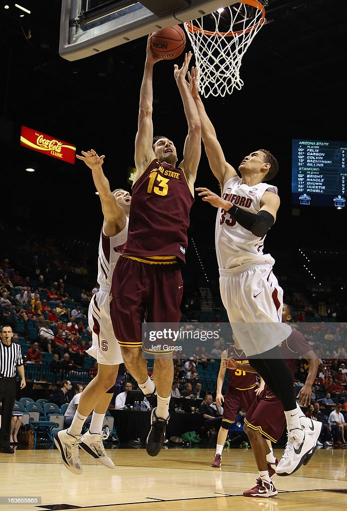 Jordan Bachynski #13 of the Arizona State Sun Devils drives to the basket past Dwight Powell #33 of the Stanford Cardinal for a dunk in the first half during the first round of the Pac 12 Tournament at the MGM Grand Garden Arena on March 13, 2013 in Las Vegas, Nevada. Arizona State defeated Stanford 89-88 in overtime.