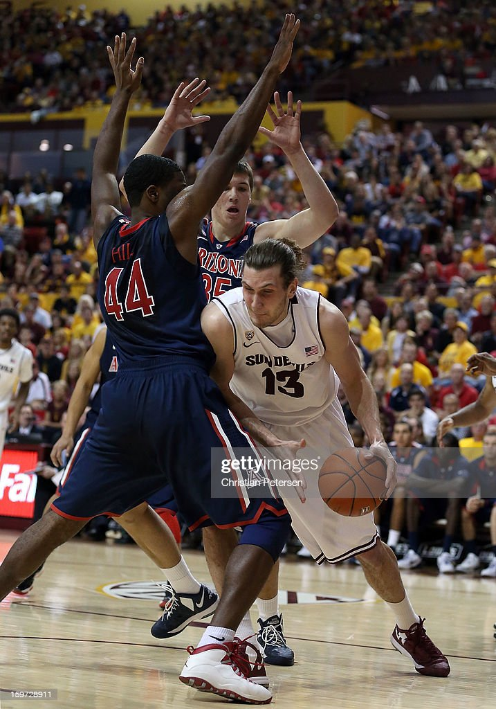 Jordan Bachynski #13 of the Arizona State Sun Devils is defended by Solomon Hill #44 and <a gi-track='captionPersonalityLinkClicked' href=/galleries/search?phrase=Kaleb+Tarczewski&family=editorial&specificpeople=8047518 ng-click='$event.stopPropagation()'>Kaleb Tarczewski</a> #35 of the Arizona Wildcats during the college basketball game at Wells Fargo Arena on January 19, 2013 in Tempe, Arizona. The Wildcats defeated the Sun Devils 71-54.