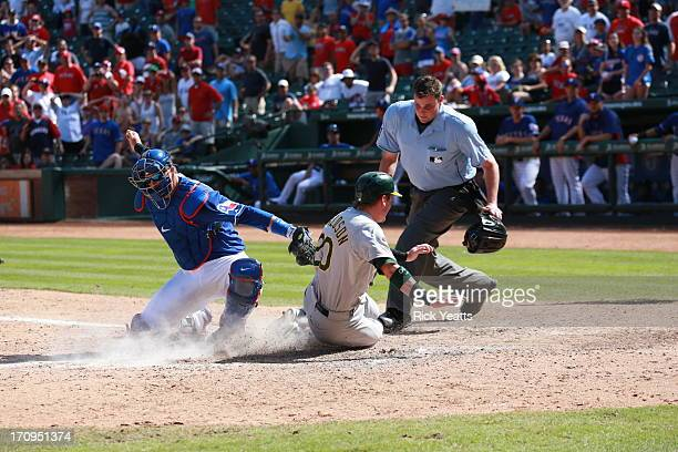 Jordan Baker looks on as AJ Pierzynski of the Texas Rangers tags out Josh Donaldson of the Oakland Athletics in the ninth inning at Rangers Ballpark...