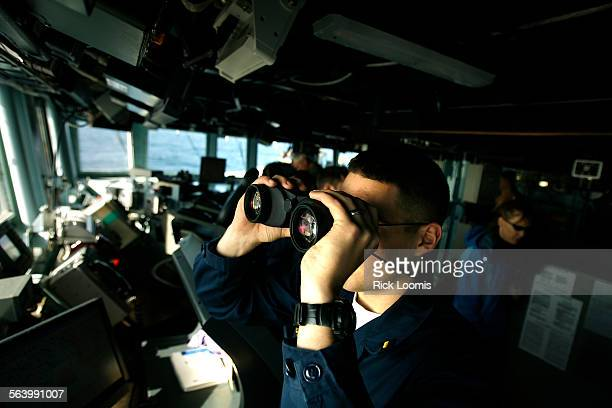 GM2 Jordan Bennett watches for marine mammals with binoculars during an active sonar training exercise on board the destroyer USS Momsen 80 miles off...