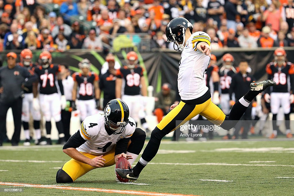 5379ad60a Jordan Berry 4 of the Pittsburgh Steelers holds the ball as Chris Boswell  ...