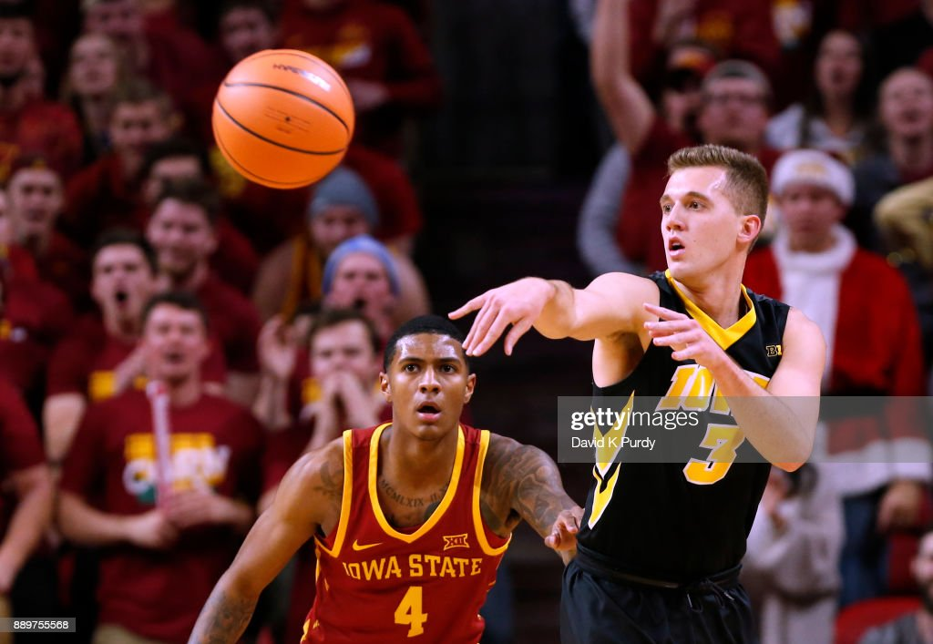 Jordan Bohannon #3 of the Iowa Hawkeyes passes the ball while Donovan Jackson #4 of the Iowa State Cyclones defends in the first half of play at Hilton Coliseum on December 7, 2017 in Ames, Iowa.