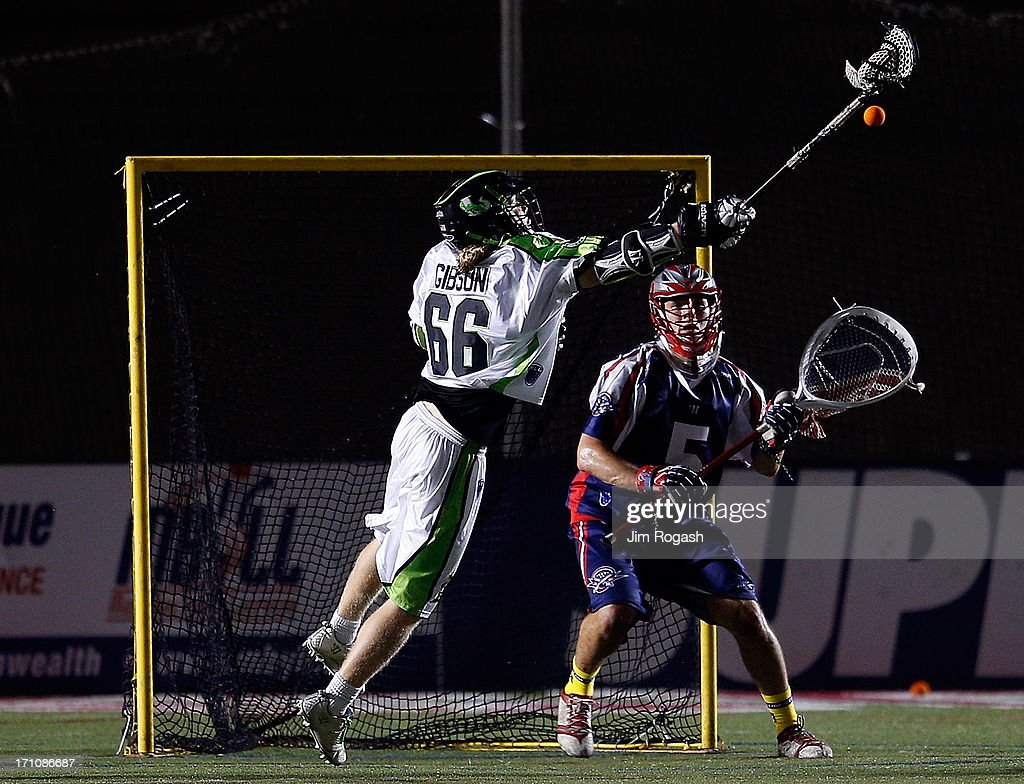 Jordan Burke #5 of the Boston Cannons defends the net as Matt Gibson #66 of the New York Lizards shoots on net in the second half at Harvard Stadium on June 21, 2013 in Boston, Massachusetts.