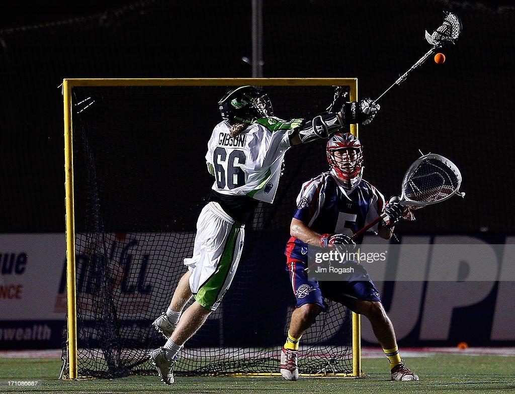 Jordan Burke #5 of the Boston Cannons defends the net as Matt Gibson #66 of the New York Lizards shoots on net in the second half at Harvard Stadium on June 21, 2013 in Boston, Massachusetts.