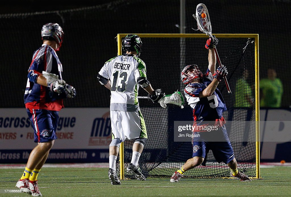 Jordan Burke #5 of the Boston Cannons makes a save under pressure from Stephen Berger #13 of the New York Lizards in the second half at Harvard Stadium on June 21, 2013 in Boston, Massachusetts.
