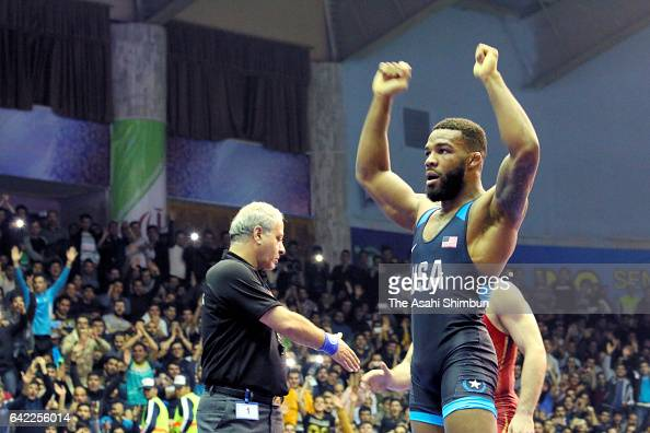 Jordan Burroughs of the United States celebrates while Iranian fans cheer after beating Atsamaz Sanakoev of Russia in the Group A Round 2 match...