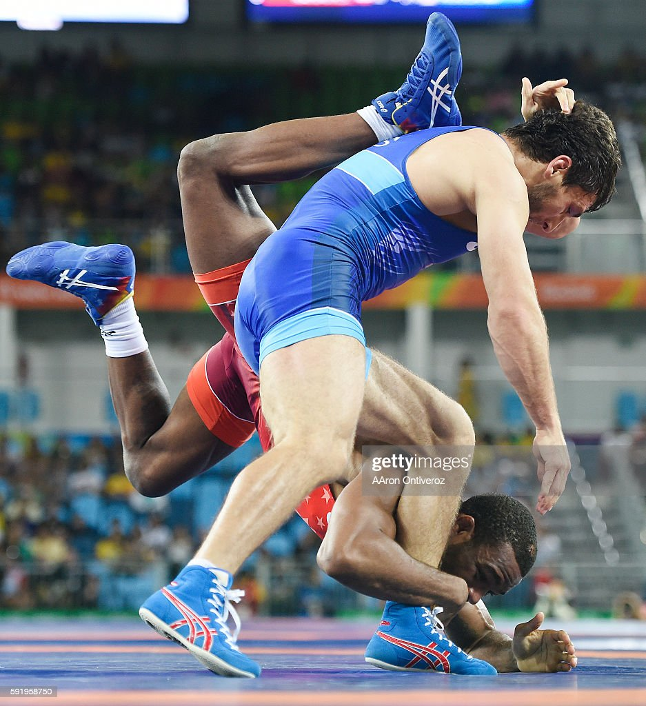 Jordan Burroughs of the United States goes upside down as he reaches for an ankle while defending a shot by Aniuar Geduev of Russia during Geduev's...