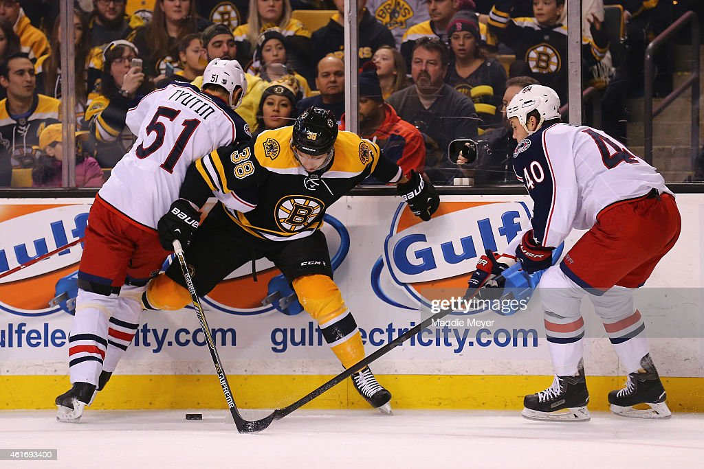Jordan Caron of the Boston Bruins and Fedor Tyutin of the Columbus Blue Jackets battle for control of the puck during the first period at TD Garden...