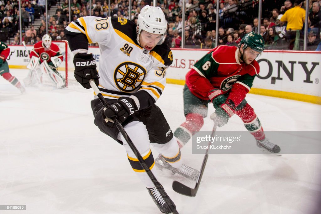 Jordan Caron of the Boston Bruins and Marco Scandella of the Minnesota Wild battle for the puck during the game on April 8 2014 at the Xcel Energy...