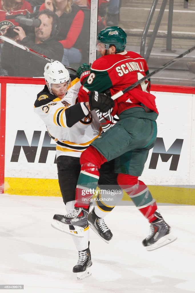 Jordan Caron of the Boston Bruins checks Marco Scandella of the Minnesota Wild during the game on April 8 2014 at the Xcel Energy Center in St Paul...