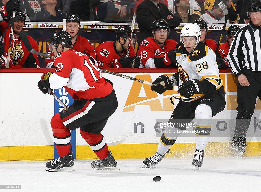 Jordan Caron #38 of the Boston Bruins chips the puck past <a gi-track='captionPersonalityLinkClicked' href=/galleries/search?phrase=Jason+Spezza&family=editorial&specificpeople=202023 ng-click='$event.stopPropagation()'>Jason Spezza</a> #19 of the Ottawa Senators during an NHL game at Scotiabank Place on April 5, 2012 in Ottawa, Ontario, Canada.