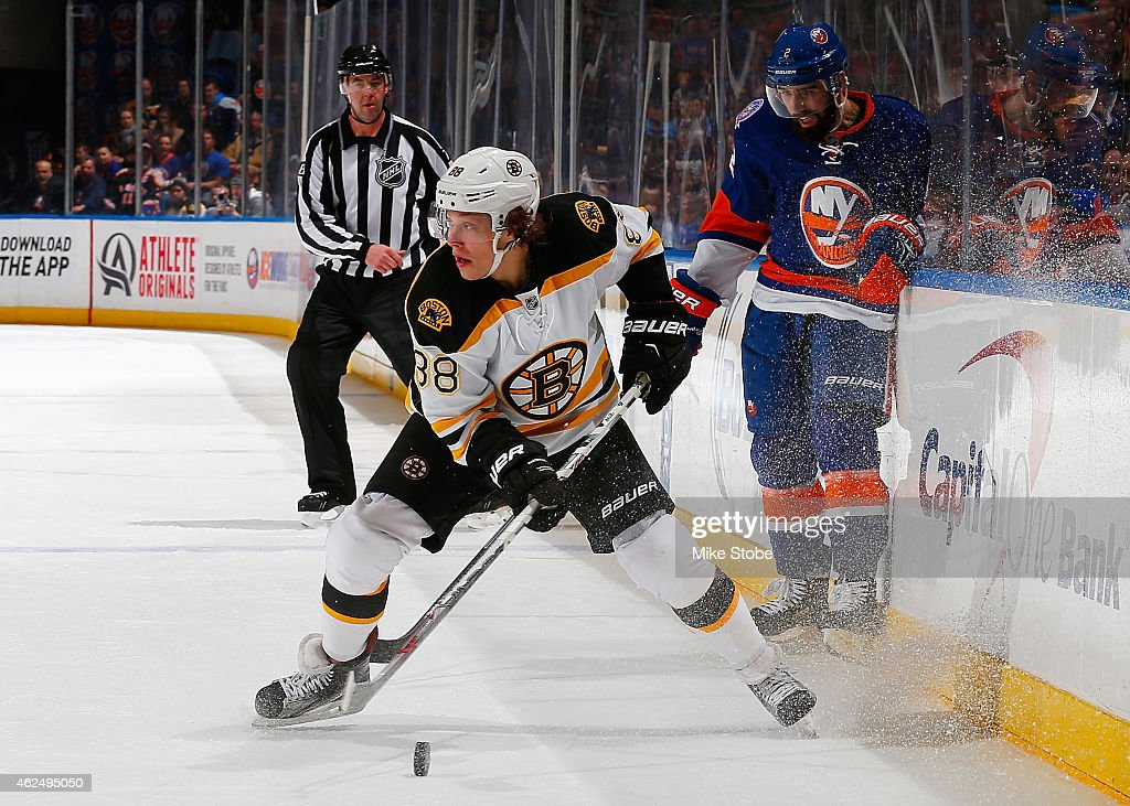 Jordan Caron of the Boston Bruins is pursued by Nick Leddy of the New York Islanders at Nassau Veterans Memorial Coliseum on January 29 2015 in...