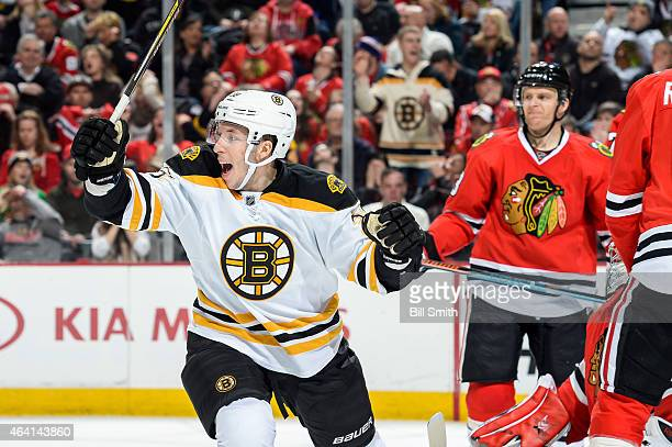 Jordan Caron of the Boston Bruins reacts after the Bruins scored against the Chicago Blackhawks in the second period as Kris Versteeg stands in the...
