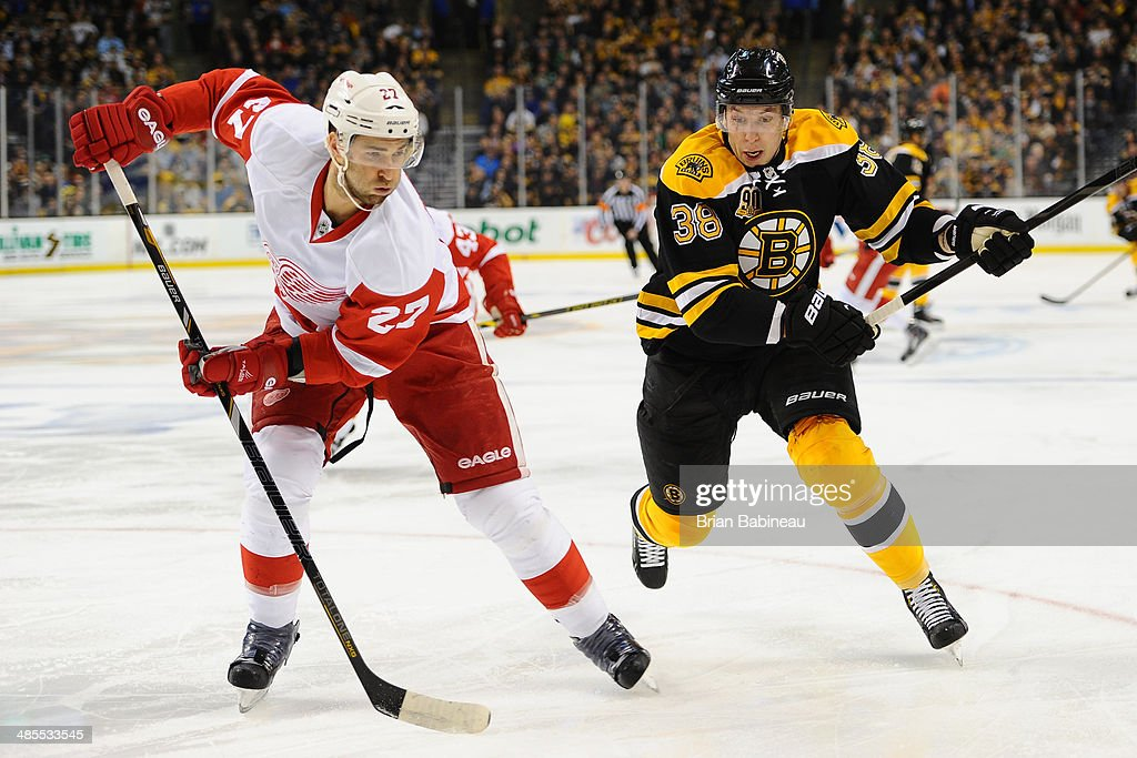 Jordan Caron of the Boston Bruins skates against Kyle Quincey of the Detroit Red Wings in Game One of the First Round of the 2014 Stanley Cup...