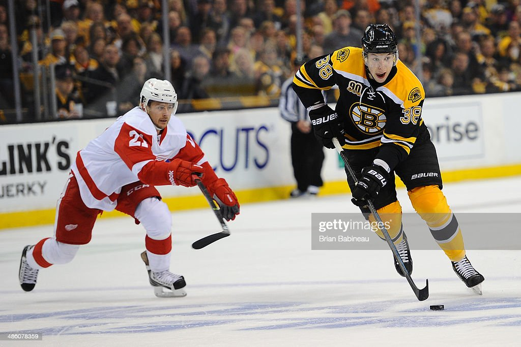 Jordan Caron of the Boston Bruins skates with the puck against Tomas Tatar of the Detroit Red Wings in Game Two of the First Round of the 2014...