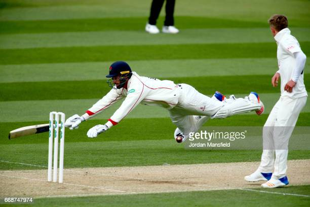 Jordan Clark of Lancashire dives to make his ground during day two of the Specsavers County Championship Division One match between Surrey and...