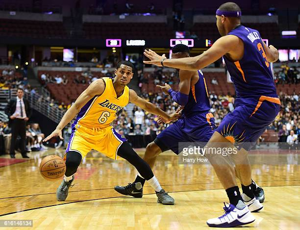 Jordan Clarkson of the Los Angeles Lakers keeps his dribble from Leandro Barbosa and Jared Dudley of the Phoenix Suns during a preseason game at...