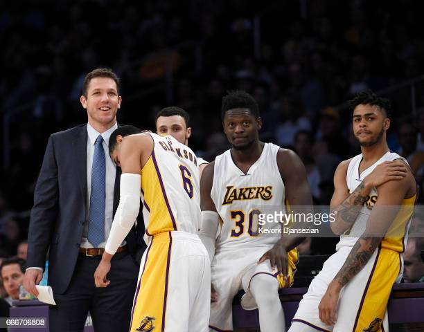 Jordan Clarkson of the Los Angeles Lakers puts his head on the shoulder of head coach Luke Walton of the Los Angeles Lakers as he waits to check back...