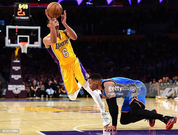 Jordan Clarkson of the Los Angeles Lakers scores on his off balance shot as he is fouled by Russell Westbrook of the Oklahoma City Thunder during a...