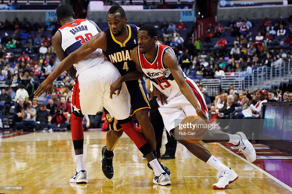 Jordan Crawford #15 of the Washington Wizards dribbles the ball around Sam Young #4 of the Indiana Pacers and teammate Earl Barron #30 during the first half at Verizon Center on November 19, 2012 in Washington, DC.