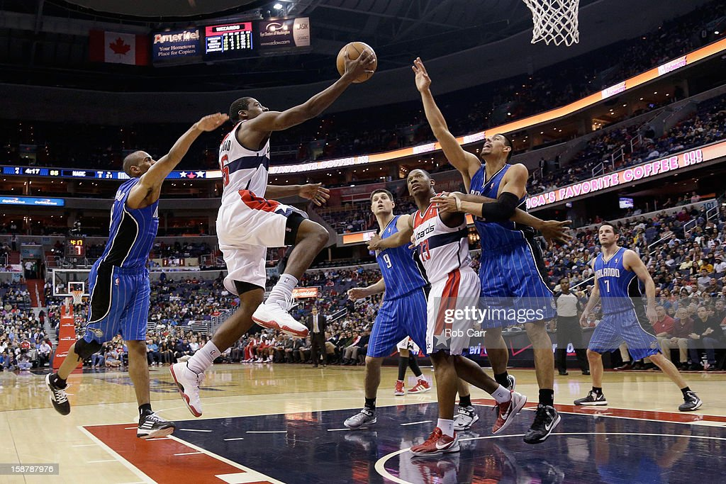 Jordan Crawford #15 (C) of the Washington Wizards puts up a shot in front of Arron Afflalo #4 (L) and Gustavo Ayon #19 (R)of the Orlando Magic during the second half of the Wizards 105-97 win at Verizon Center on December 28, 2012 in Washington, DC.