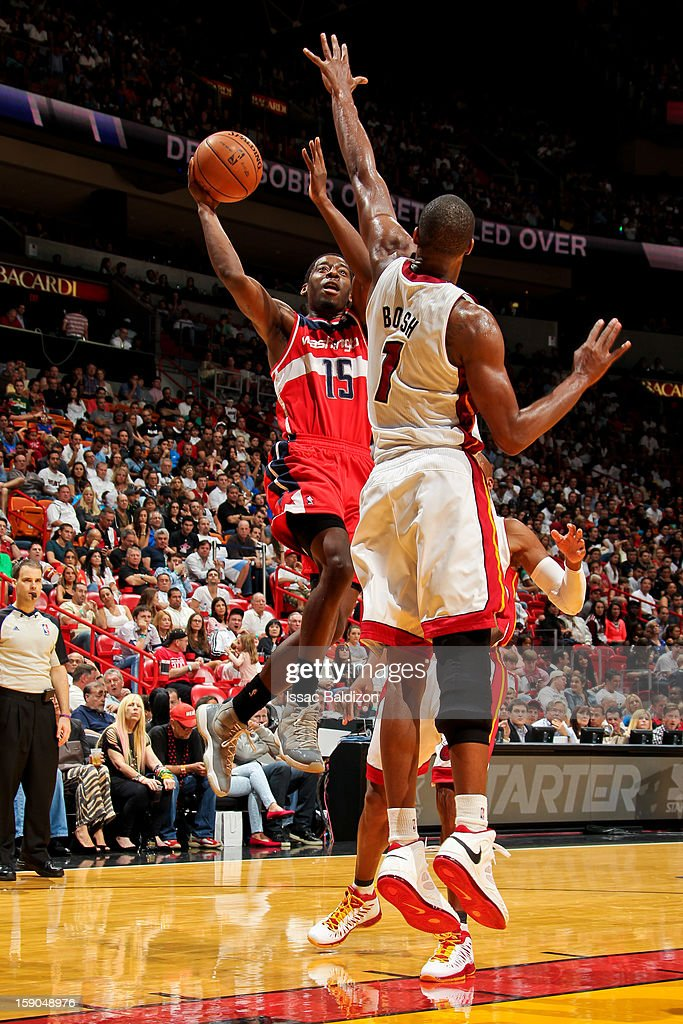 Jordan Crawford #15 of the Washington Wizards shoots against Chris Bosh #1 of the Miami Heat on January 6, 2013 at American Airlines Arena in Miami, Florida.