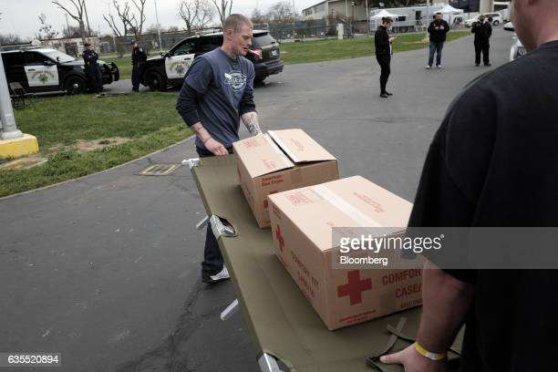 Jordan Cross Ministries of Oroville volunteers carry boxes and a cot at the Silver Dollar Fairgrounds evacuation center in Chico California US on...