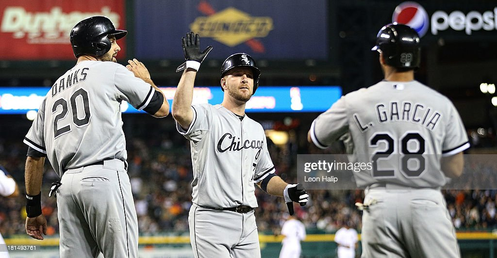 Jordan Danks #20 and Jeff Keppinger #7 of the Chicago White Sox celebrate with teammate Leury Garcia #28 after scoring on the double by Bryan Anderson #39 in the ninth inning of the game against the Detroit Tigers at Comerica Park on September 21, 2013 in Detroit, Michigan.