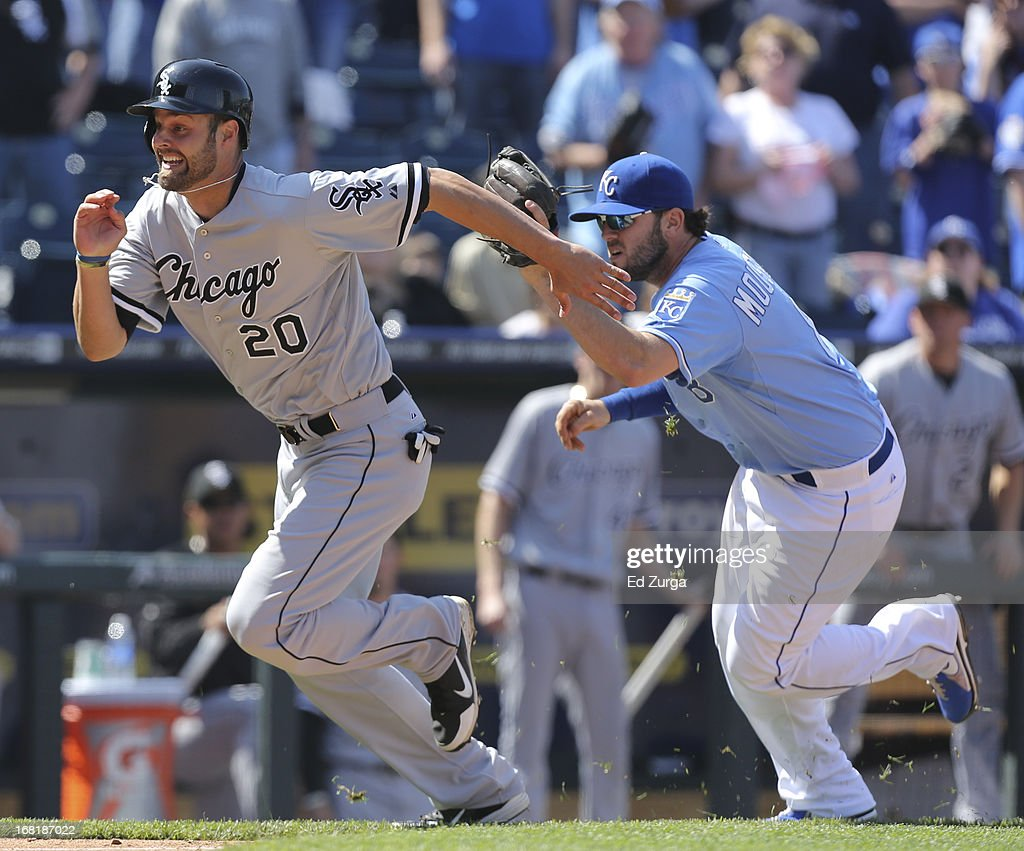 Jordan Danks #20 of the Chicago White Sox is chased by <a gi-track='captionPersonalityLinkClicked' href=/galleries/search?phrase=Mike+Moustakas&family=editorial&specificpeople=6780077 ng-click='$event.stopPropagation()'>Mike Moustakas</a> #8 of the Kansas City Royals as he is caught in a rundown in the ninth inning at Kauffman Stadium on May 6, 2013 in Kansas City, Missouri.