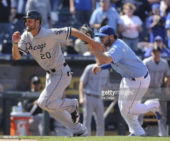 Jordan Danks of the Chicago White Sox is chased by Mike Moustakas of the Kansas City Royals as he is caught in a rundown in the ninth inning at...