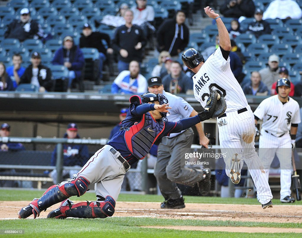 <a gi-track='captionPersonalityLinkClicked' href=/galleries/search?phrase=Jordan+Danks&family=editorial&specificpeople=2364706 ng-click='$event.stopPropagation()'>Jordan Danks</a> #20 of the Chicago White Sox scores as <a gi-track='captionPersonalityLinkClicked' href=/galleries/search?phrase=Kurt+Suzuki&family=editorial&specificpeople=682702 ng-click='$event.stopPropagation()'>Kurt Suzuki</a> #8 of the Minnesota Twins makes a late tag during the seventh inning in game one of a doubleheader on September 13, 2014 at U.S. Cellular Field in Chicago, Illinois.