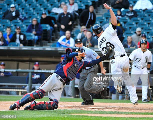 Jordan Danks of the Chicago White Sox scores as Kurt Suzuki of the Minnesota Twins makes a late tag during the seventh inning in game one of a...