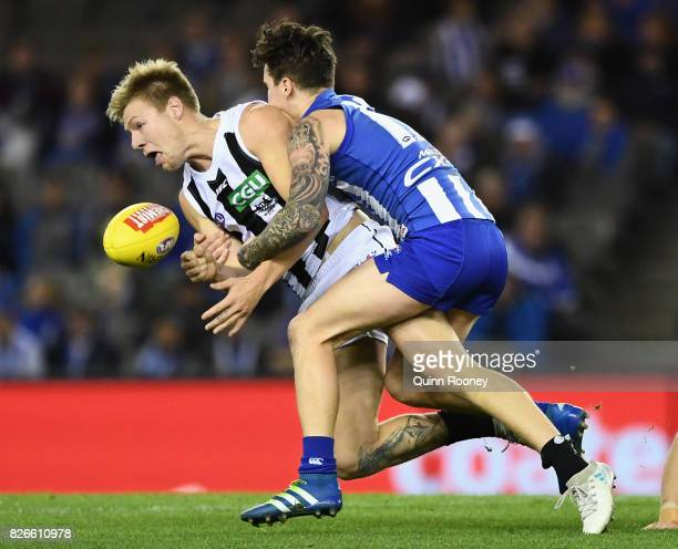 Jordan De Goey of the Magpies handballs whilst being tackled by Aaron Mullett of the Kangaroos during the round 20 AFL match between the North...