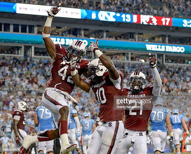 Jordan Diggs Skai Moore and Isaiah Johnson of the South Carolina Gamecocks celebrate after Moore's interception of Marquise Williams of the North...