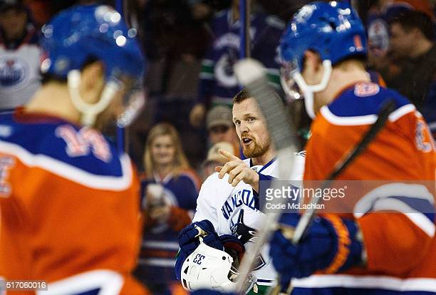 Jordan Eberle and Griffin Reinhart of the Edmonton Oilers skate in the foreground as Henrik Sedin of the Vancouver Canucks gestures on March 18 2016...